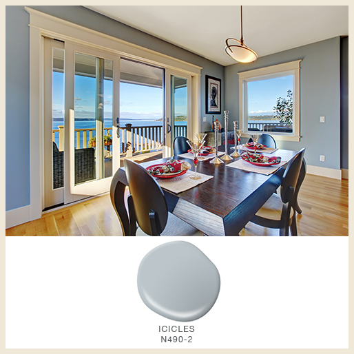 A dining room with a lake view and walls painted in light blue-toned gray color called Icicles.