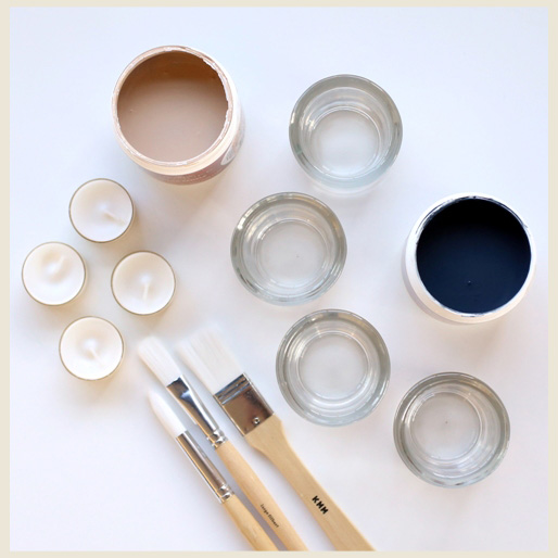 A frame showing all materials needed to paint glass votives: paint, assortment of small paintbrushes, glass votives and tea lights.
