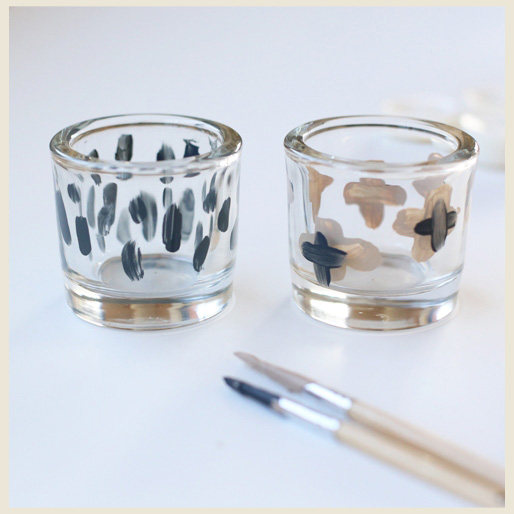 A frame showing two glass votives with different paint designs.