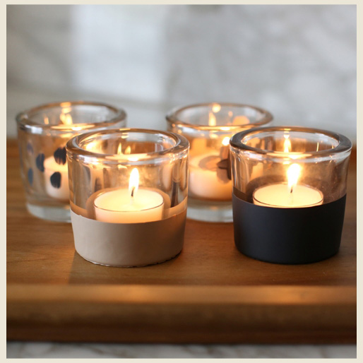 Four painted votives with dark gray and being paint. Lit tealights inside glass votives.