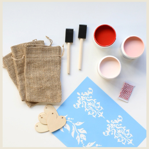 Materials to decorate a Valentine's burlap gift bag. Material included: small foam paintbrushes, paper towels, stencils, paper hearts, twine string, small burlap gift bags and three different paint sample containers with pink colors.