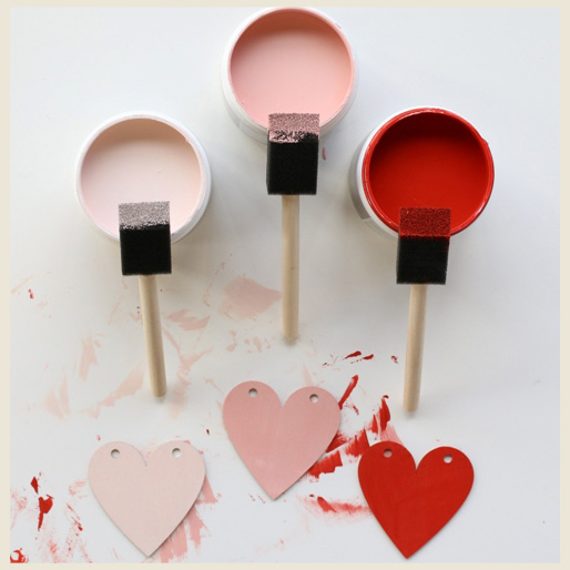 A frame showing painted paper hearts in three different pink-red tones.