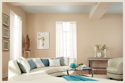 An airy and well lit living room featuring light pastel peach walls and blue ceiling.