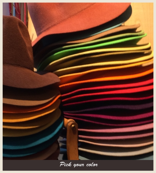 Two stacks of many different colors of hats.