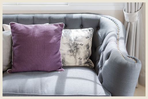 A studded gray sofa with decorative pillows.