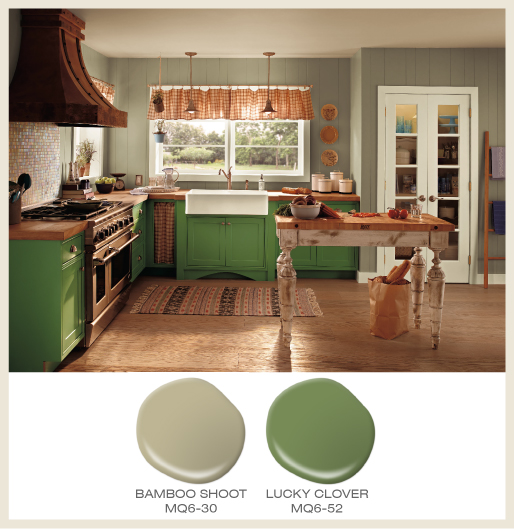 A cottage style kitchen with green cabinets coordinated with sage green walls.
