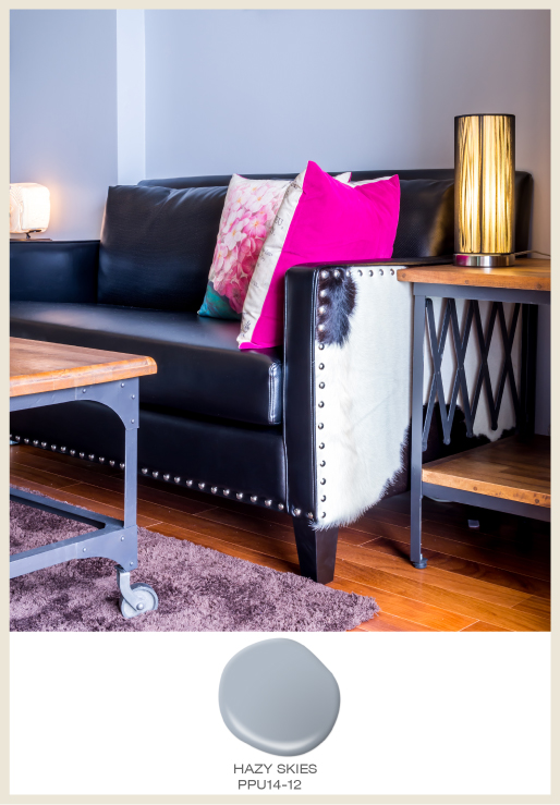 A studded black leather sofa with cowhide upholstery side accents.