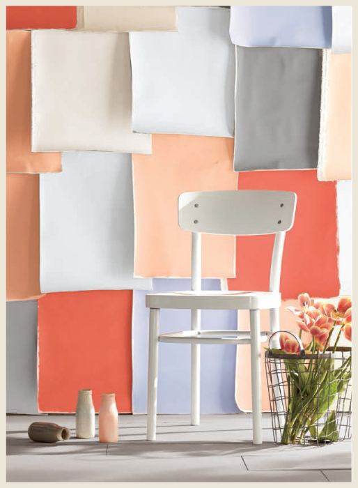 A wall covered with layers of colorful construction paper sheets.