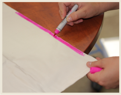 A woman's hand holding a pillow case and coloring a dye line to create an ombre look.
