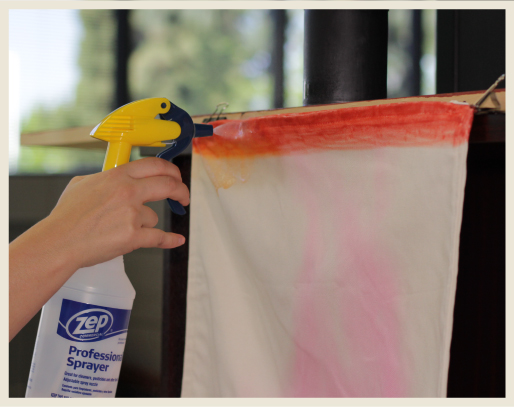A woman's hand holding spray bottle with alcohol, spraying dye line and starting to disperse to create an ombre look.