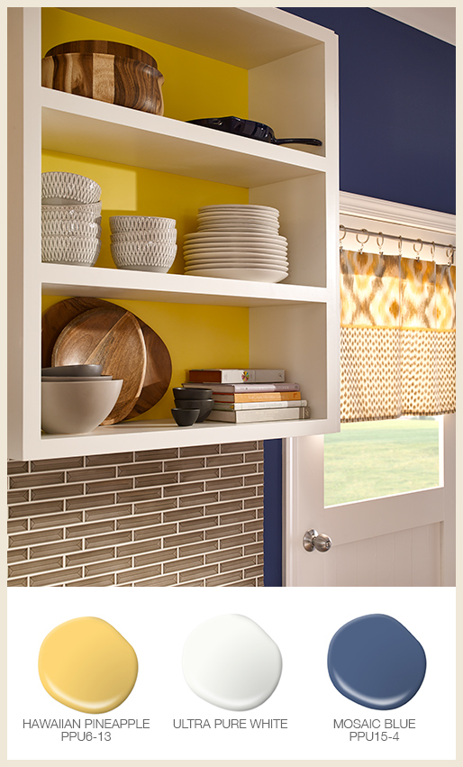 A close up image of open kitchen cabinets with bright yellow color behind the shelves.