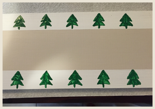 Wood board after being painted with borders and pine tree stencils.