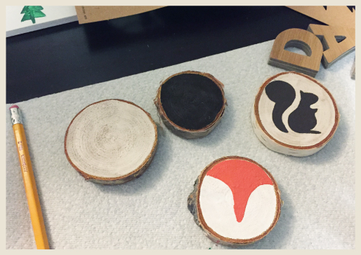 Birch rings being painted with woodland creature stencils and freehand designs..