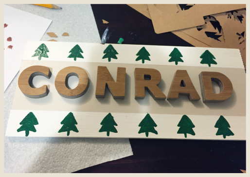 Wood board after being painted, stenciled and mounted name letters.
