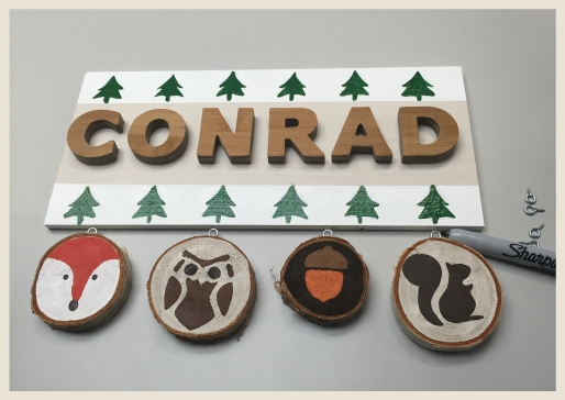 Birch rings with woodland creatures being mounted to the name plaque.