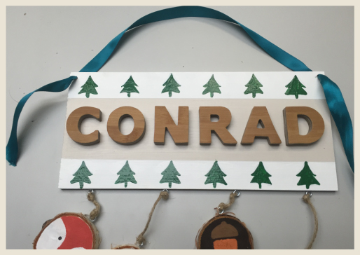 Name plaque with holes to add blue ribbon as a hanger.