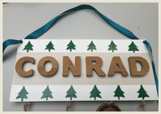 Name plaque with blue ribbon tied in as a hanger.