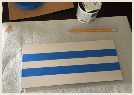 A wood board with blue tape sections.