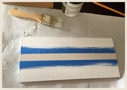 A wood board with tape sections and paint to create a border.