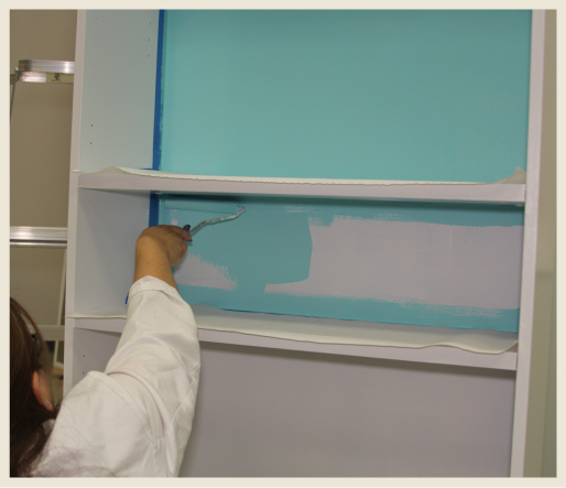 A woman using a small paint roller to paint a narrow back part of a bookcase.