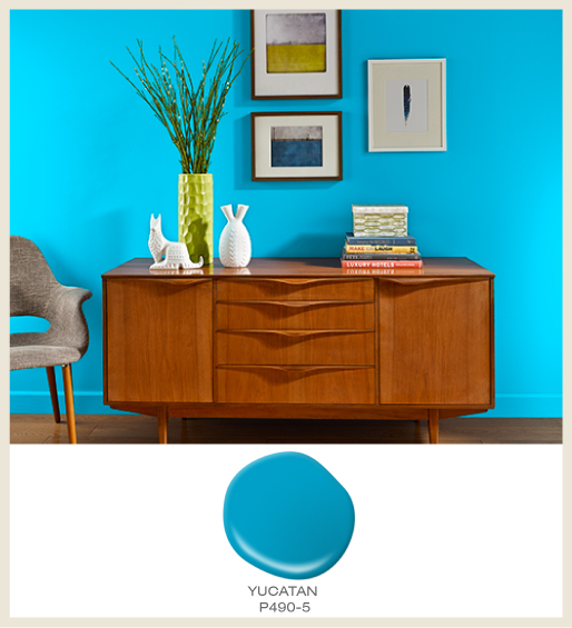 A dining room with a bright blue accent wall, featured color is Yucatan.