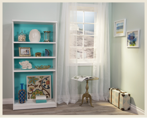 A relaxing interior environment of a beach cottage entry area over-looking the beach. A bookshelf painted with white paint and aqua colors, decorated with multiple nautical objects.