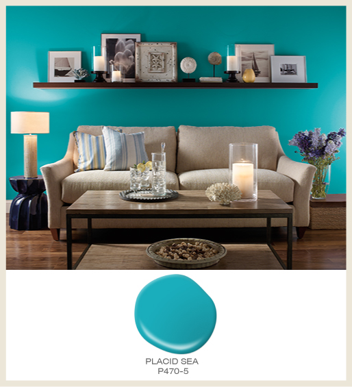 A coastal style living room with a bright blue wall and sand-tone elements, featured color is Placid Sea.