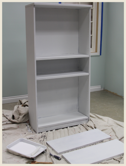 A bookcase with a coat of primer.