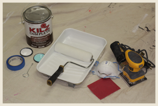 DYI painting supplies. Paint can, can opener, drop-cloth, roller, blue tape, face mask and electric sander ready for DIY work.