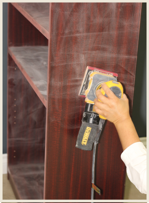 A woman's hand using an electric wood sander to strip down a wooden surface in preparation for furniture renovation.