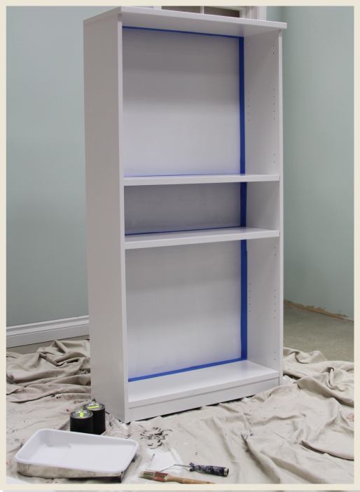 A bookcase with blue tape outlining where paint will applied.