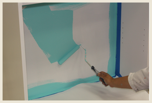 A woman's hand rolling paint on the back area of a bookcase, using blue tape as a guide.
