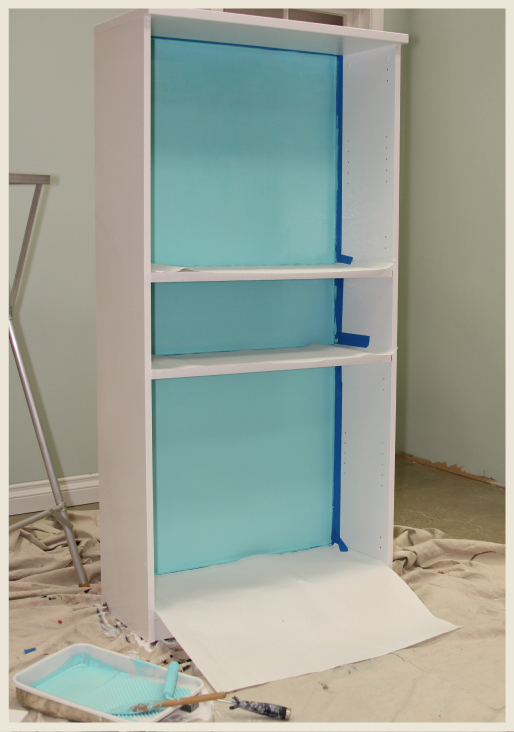 A bookcase after it has been painted, blue painter's tape and paper still attached.