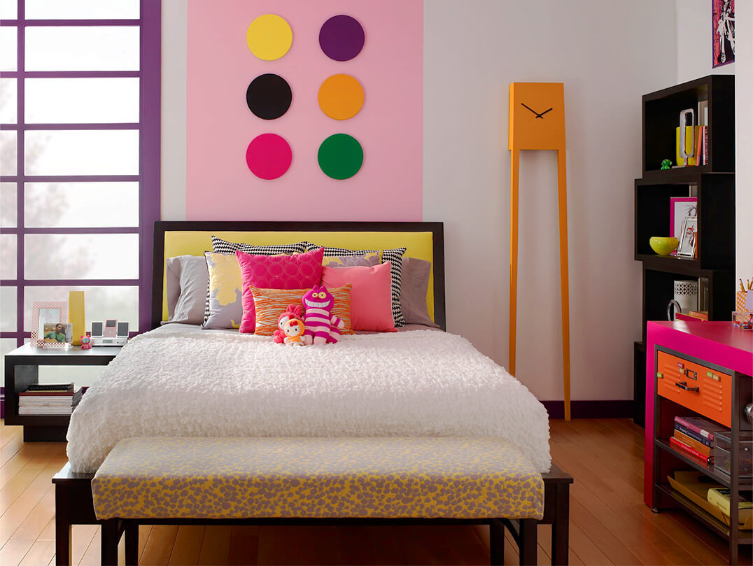 This image shows a tween girls bedroom. It has a modern look to it with a stripe on the wall painted in Little Princess. Remaining walls are painted in Polar Bear and trim is painted in Proper Purple.  There is a small night stand to the left of the bed decorated with photos, books and an ipod with speaker.  There is a wall unit to the left with books, photos, and other decoration elements. There is also a pink desk with books and notebooks.  To the edge of the bed is a leopard style seat.  And lastly there is a tall modern orange clock.