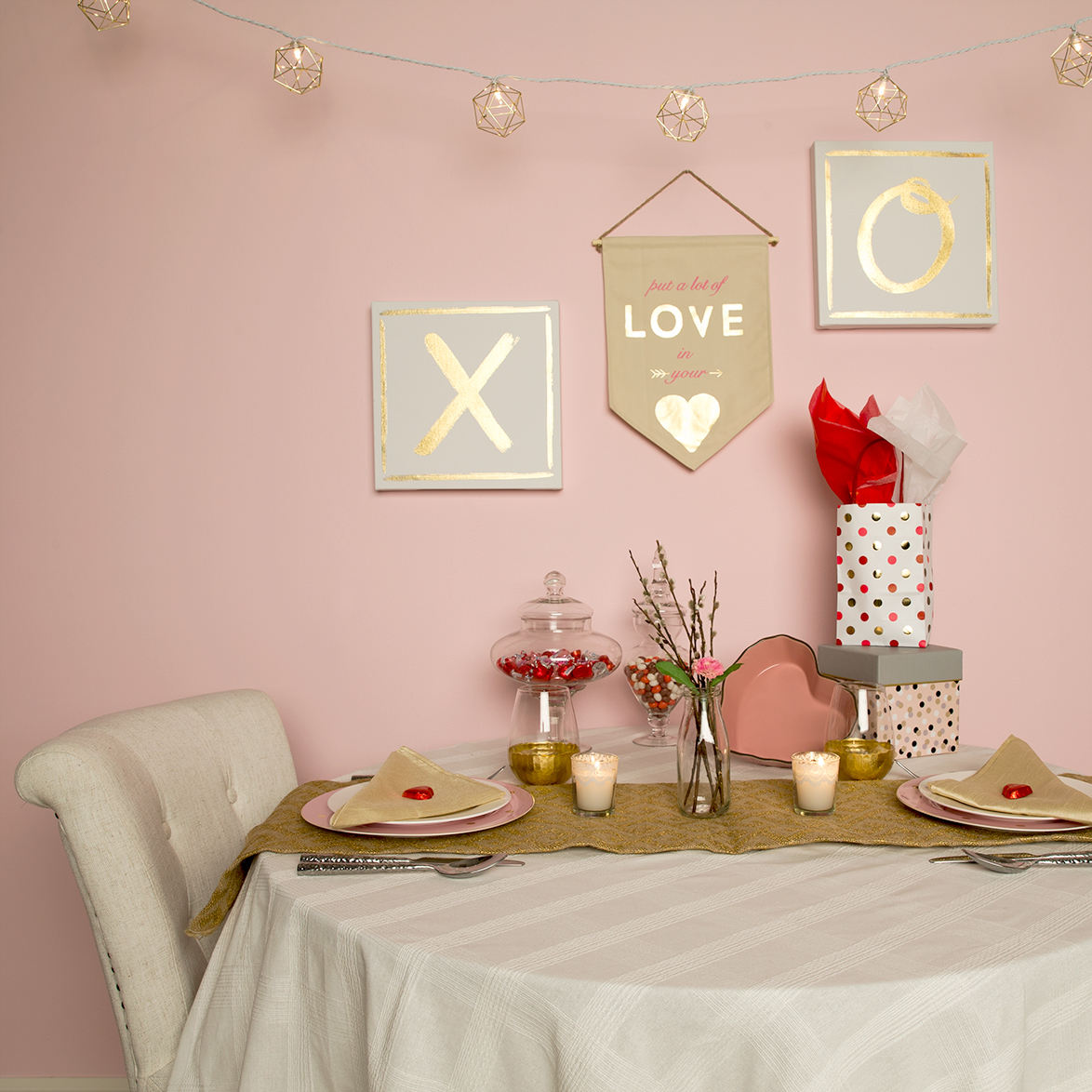 """This image shows a creative way to set up a Valentines Day table setting. The wall is painted in Funhouse which is a muted pink. The wall has a X and O on canvas to symbolize hugs and kisses. There is a sign that says """"put a lot of love in your heart"""" and also hanging overhead is small lights.  The table setting has a large plate, small plate, napkin and two cups.  There are chocolates on the table as well and two gifts.  To finalize the look is a flower at the middle of the table and two candles."""