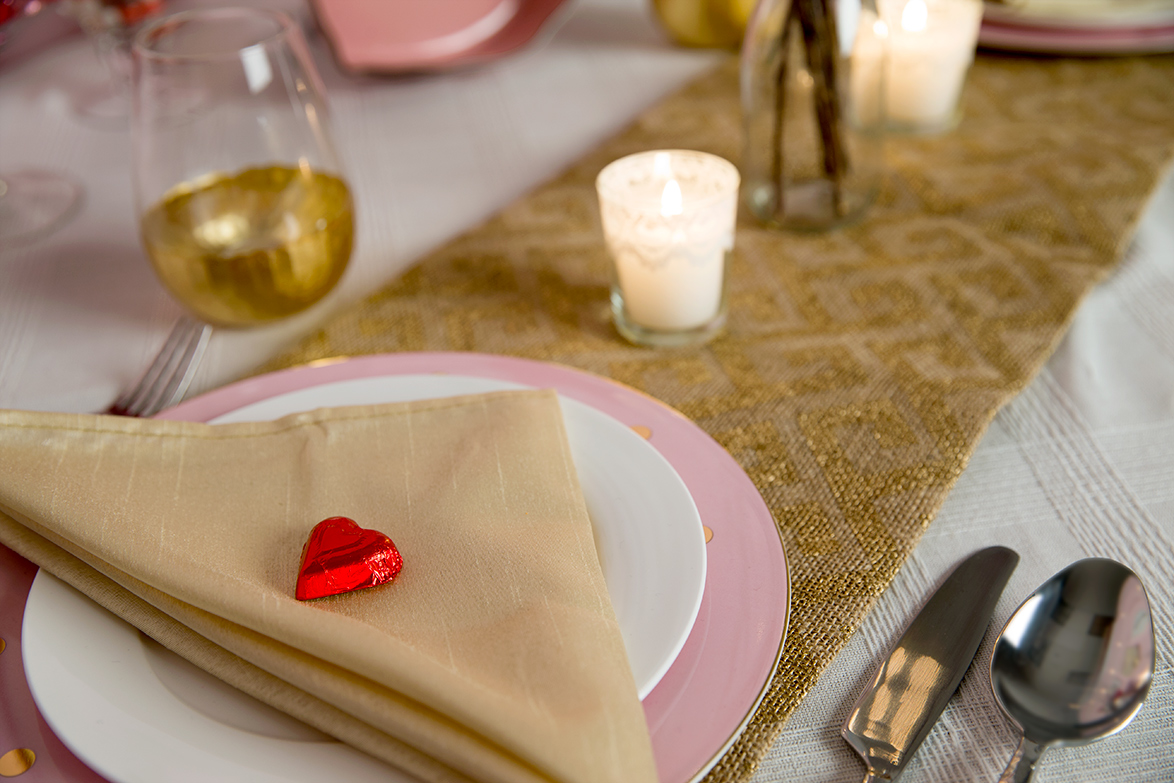 This is a close up of the table setting with the plates, silverware, candle and cup.