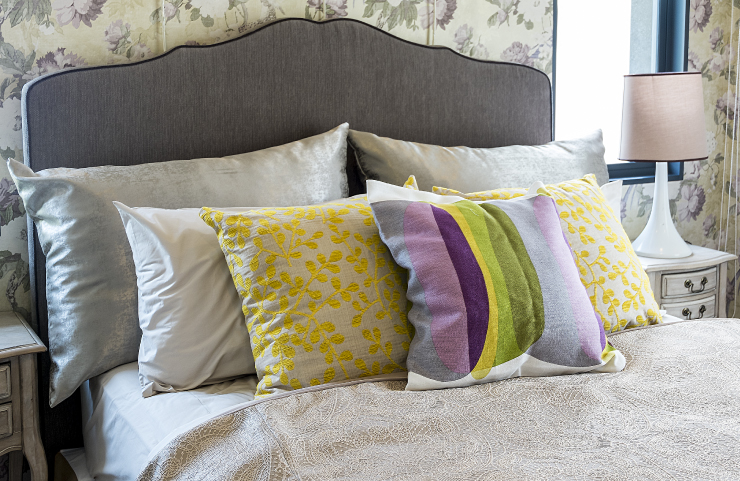 A bed showing pillows in mixed patterns; yellow flowers, purple yellow and green stripes, and solid.