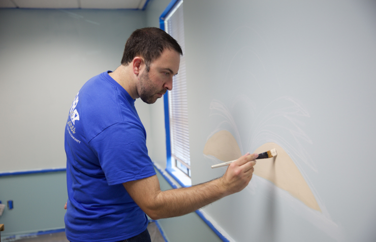 A person painting a book on a wall.