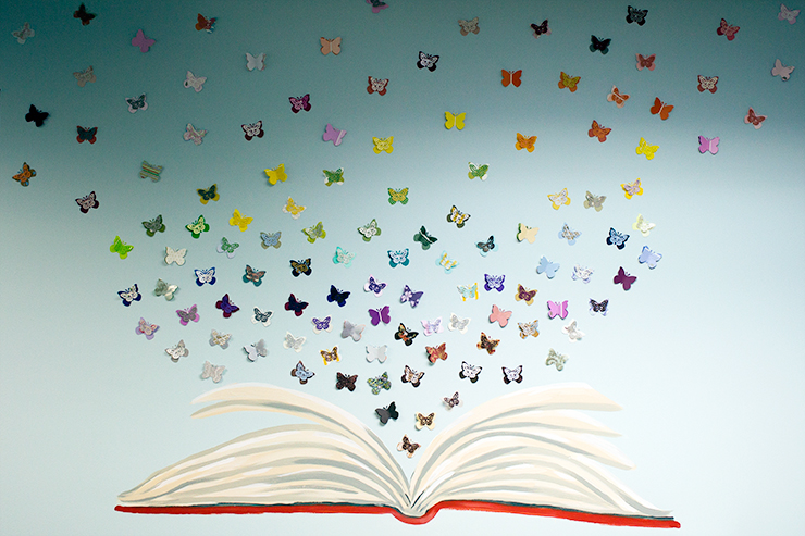 A painting on the wall showing an open book and butterflies.