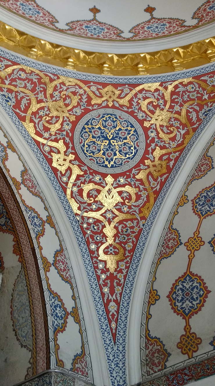 Colorful and gold paintings on the ceiling.