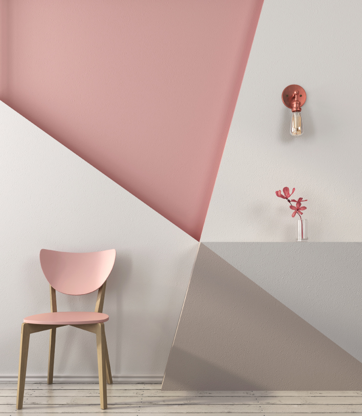 A sitting area with a pink wood chair sitting in front of a wall painted in She Loves Pink, white, beige, and gray triangular shapes.