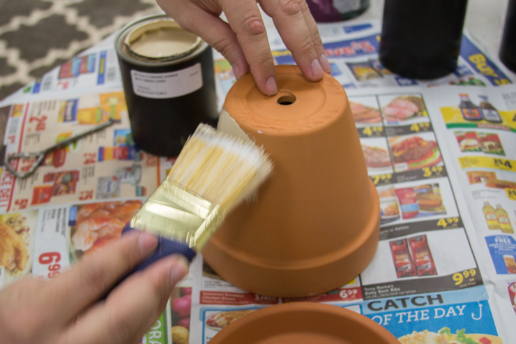 Painting the clay pot with a white colored paint.