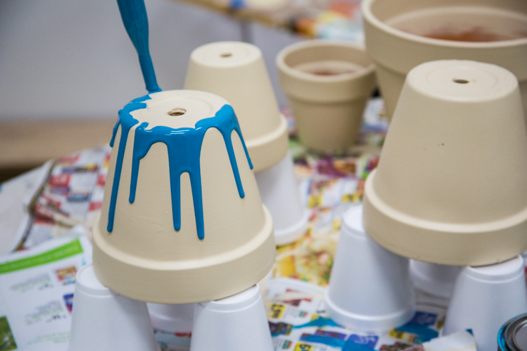 Pouring blue paint onto the clay pots from the bottom so it drips down the sides.