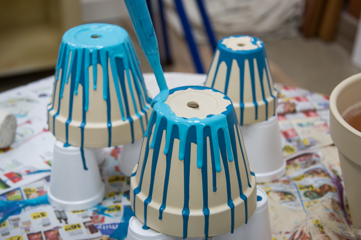 Pouring a lighter blue colored paint onto the clay pots from the bottom so it drips down the sides.