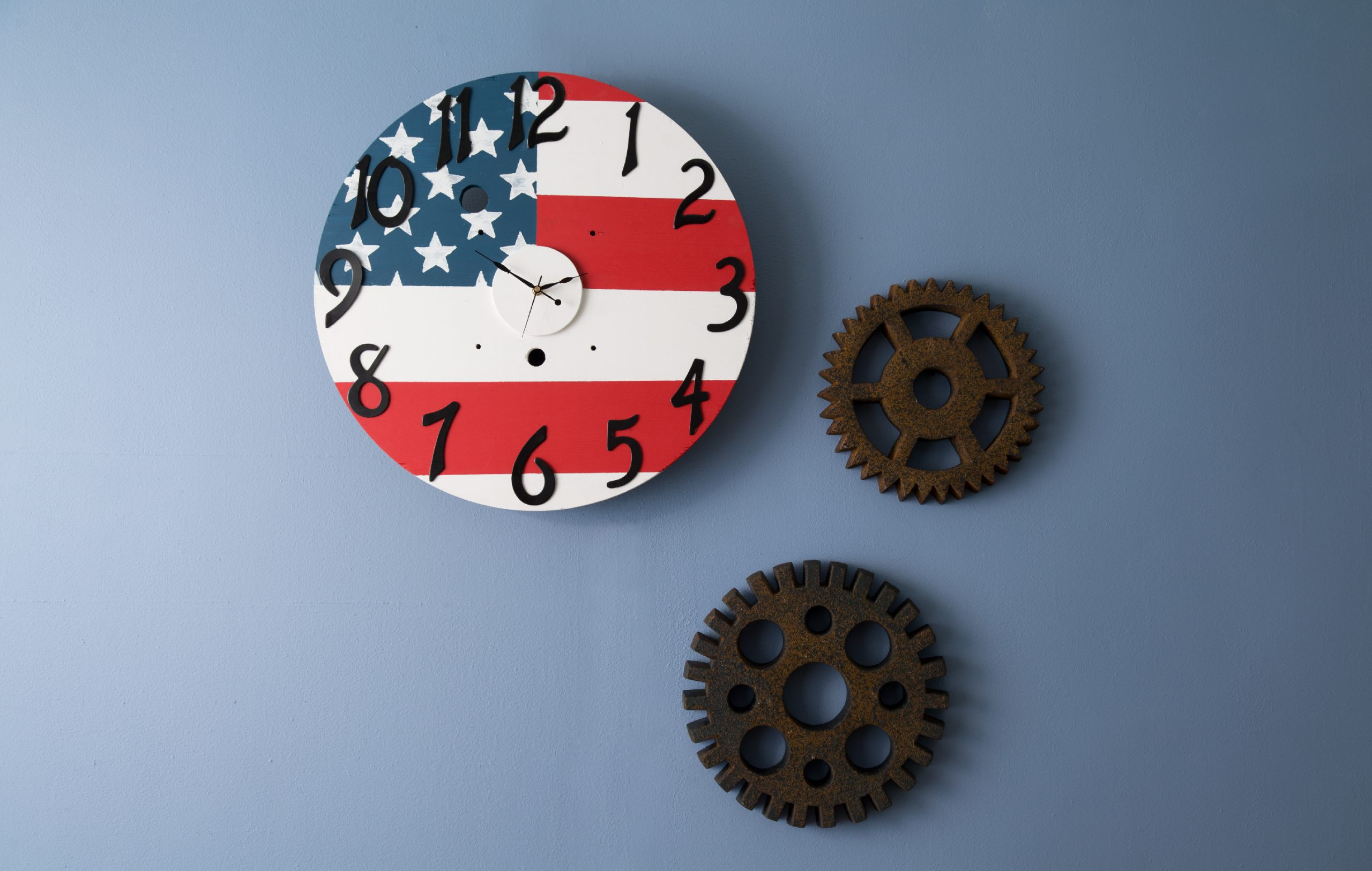 A clock hanging on a blue wall. The clock is painted to look like the patriotic flag.