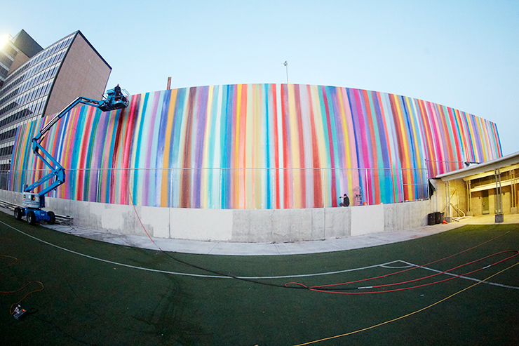 A mural on the side of the building of multi-colored stripes.