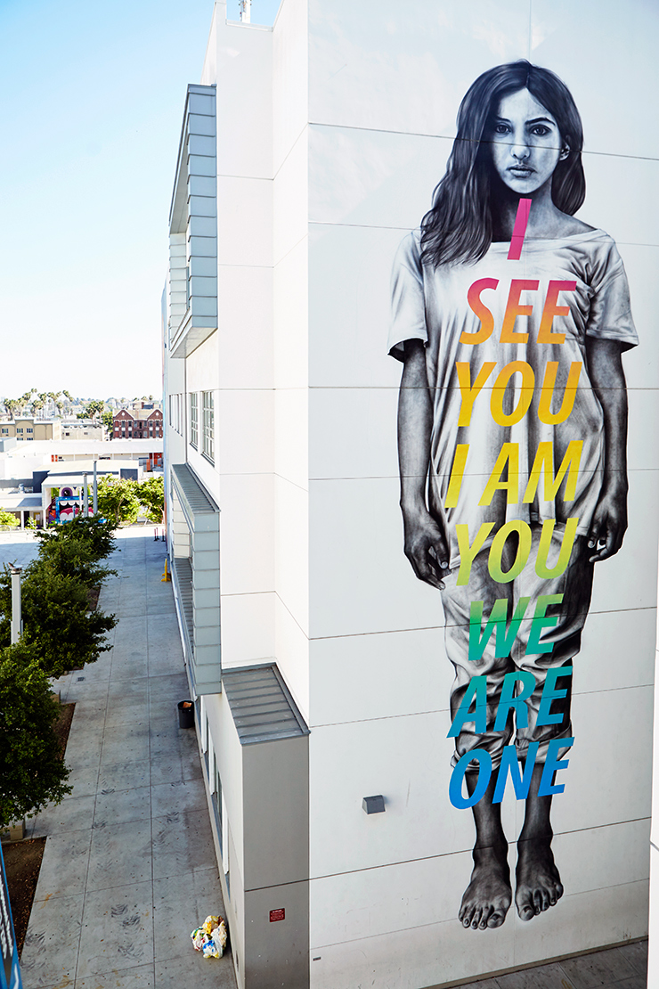 "A mural on the side of the building with the words ""I SEE YOU I AM YOU WE ARE YOU"" written on top of a drawing of a girl standing."