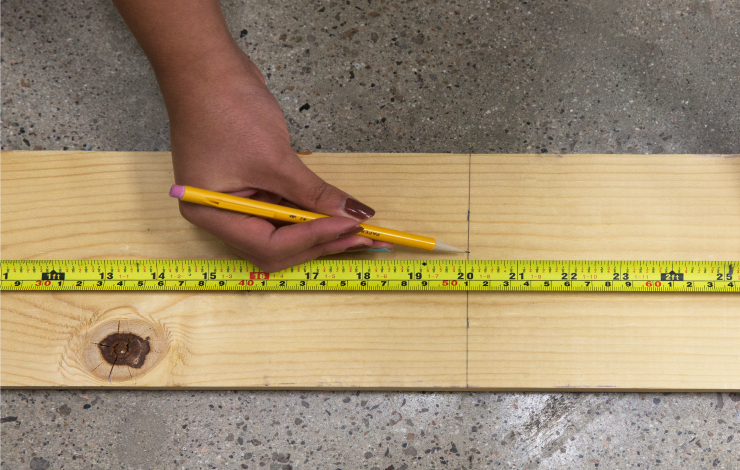 Measuring and marking a wood board to cut.