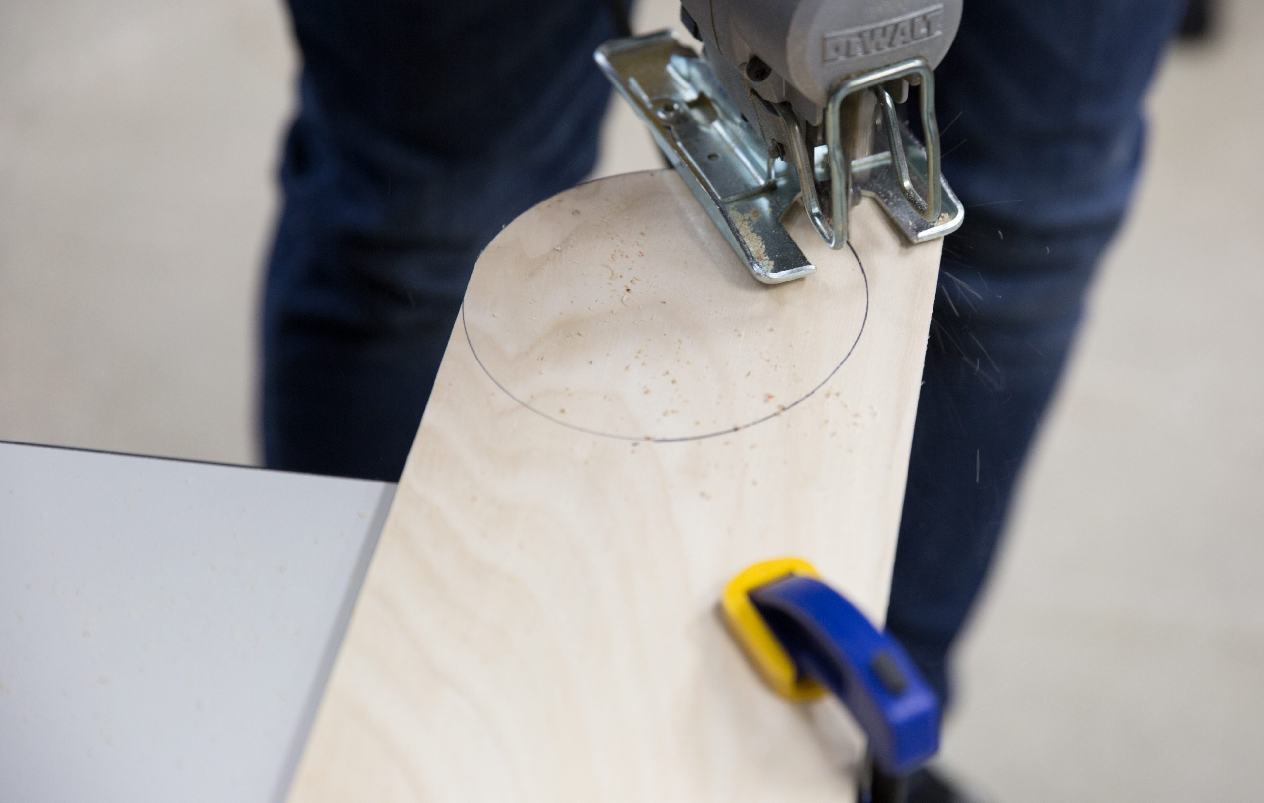 Person cutting the circle from the piece of wood.
