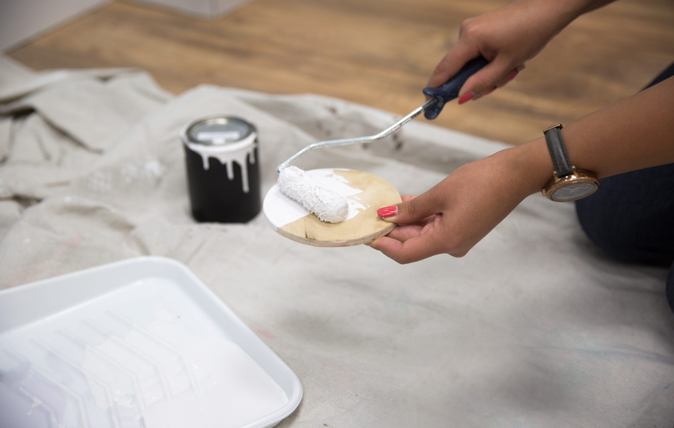 Painting the wood circle in white paint.